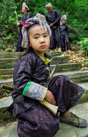 miao: GUIZHOU, CHINA - APRIL 10: Ethnic Minorities, Chinese boy at the age of 8 years old, in traditional ethnic clothing Miao tribe, holding an old musket, April 10, 2010. Basha Village, Congjiang County. Editorial