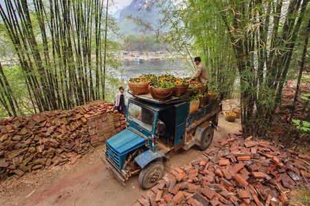autotruck: YANGSHUO, GUANGXI, CHINA - MARCH 29:  Carriage of orange crop in South-West China, March 29, 2010. Old-time blue lorry carrying a wicker basket with oranges, to the river, for further an overload the boat.