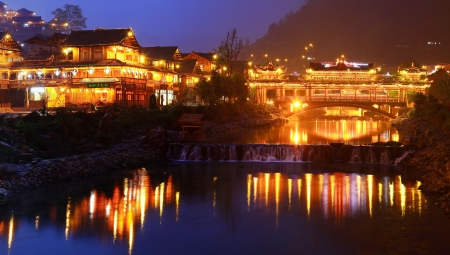 river county: GUIZHOU PROVINCE, CHINA - APRIL 18  Xijiang miao village, the largest village in Guizhou Miao ethnic minority, April 18, 2010  Night illumination of houses and a bridge over a river village in Xijiang Town  Leishan County Editorial