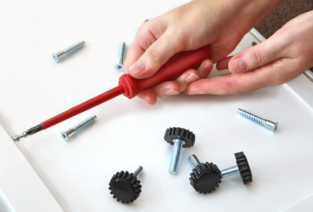 Hands screwed in a furniture panel plug with screw, with a red, cross-shaped screwdriver  On the white, furniture board, furniture lies fasteners, screws and adjustable, plastic, furniture legs, with a screw  photo