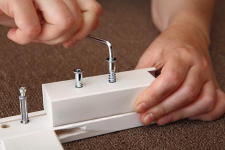 furniture hardware: mano utiliza la llave allen tornillos de madera, muebles de llave Allen en la mano una llave Allen muebles de madera