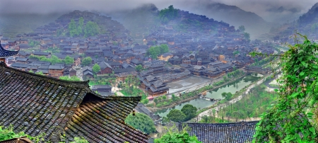 Xijiang village, Guizhou, China - April 18, 2010  Xijiang miao village, the largest village in Guizhou Miao ethnic minority, April 18, 2010   Leishan County  Houses on the mountain slopes in the morning mist and the black clouds  版權商用圖片