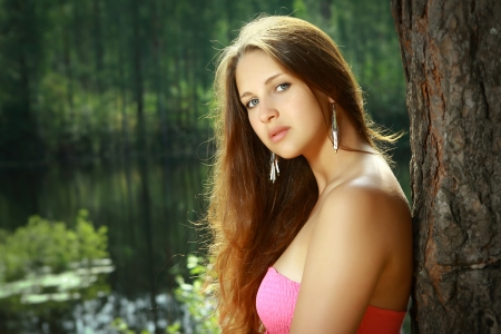 Beautiful Girl, 16 years old, with long brown hair and a pink dress, stands alone on a green background of the forest and water on a summer day in the sun  photo