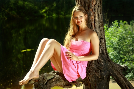 Girl caucasian appearance, 16 years old, in a pink dress, with long hair and bare feet, sitting on a tree trunk, near the dark waters of a forest lake.