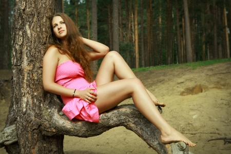 shapely legs: Teen girl 16 years old, Caucasian appearance, in a pink dress, rest on the nature, in a pine forest. A slender girl with long brown hair and bare feet, relaxing in a forest clearing, sitting on a pine branch. Beautiful, slim girl in a crumpled pink gown.