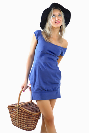 Harmonous Caucasian woman, blonde, 34 years old, wearing a short, tight, blue dress  Hat on his head to the fields, in the hands holding a wicker basket  Vertical image, isolated on white background  Girl with basket for shopping photo
