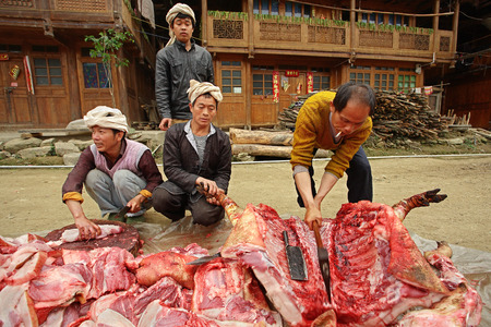 Zengchong village, Guizhou, China - April 12, 2010: Chinese peasants, farmers, pork is cut on a rural road in Zengchong village, province of Guizhou, April 12, 2010. Chinese farmer livestock, pigs carcass of cuts ax. Редакционное