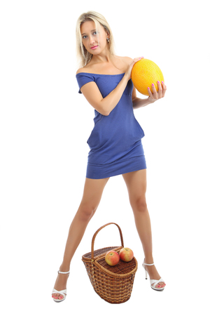 skintight: Young caucasian woman 34 years old, with blond hair in a short skin-tight blue dress, is a full-length, near the wicker basket holding a melon, vertical, isolated image on a white background.