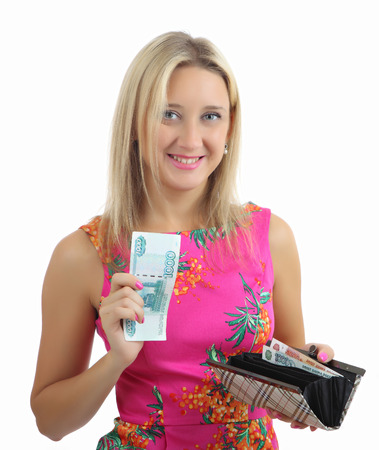 Blonde woman, caucasian 34 years old, in pink dress with flowers, smiles and holds in one hand and open purse with paper money, in the other hand, a paper bill is a thousand russian rubles. The isolated image on a white background.