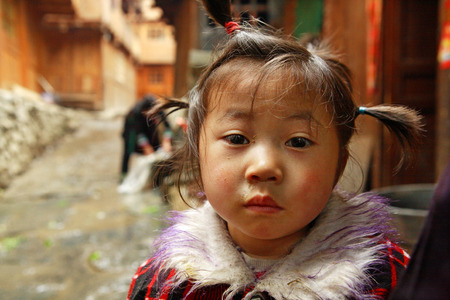 snotty: Zengchong village, Guizhou, China - April 13, 2010  Rural girl 4 years old, standing on a village street in south-west China, April 13, 2010  Asian child in the rural areas of China  Editorial