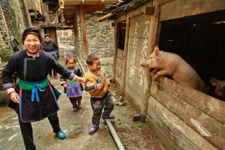 Zengchong village, Guizhou, China - April 13, 2010: The family of Chinese peasants with kids, pass past the pigsty, April 13, 2010. Asian peasant farming, pig farming, animal husbandry, rural south-west China.