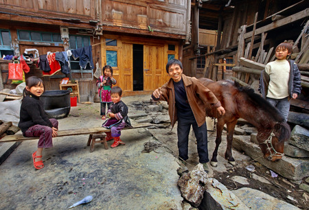 kinfolk: Zengchong village, Guizhou, China - April 12, 2010: Asian family in the countryside of southwestern China, a father and his four children, and relax in front of his wooden house in the peasant economy, April 12, 2010. Zengchong village, Guizhou, China