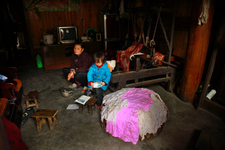 Zengchong village, Guizhou, China - April 13, 2010: Interior of the home of Chinese peasants farmers Asian woman and Child, Zengchong Dong ethnic minority Village,, Guizhou province, Southwestern China - April 13, 2010: