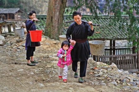 russet: Zengchong village, Guizhou, China - April 11, 2010: Asian village, a Chinese woman goes fetch water, she carries pails on yoke, and leads by the hand of the child, a girl 3 years old, a child holding a toy, Zengchong Dong village, Guizhou, China - April 1