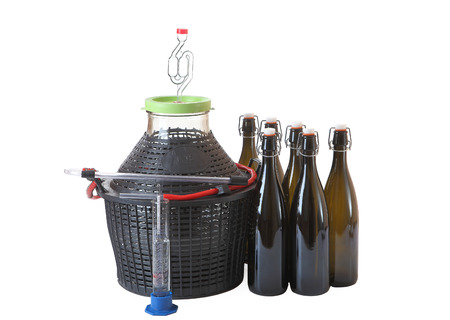 Set of equipment for home winemaking, carboy with a hose, airlock, wine bottles of dark glass with plastic caps and rubber seal, hygrometer, isolated image on white background. Banque d'images