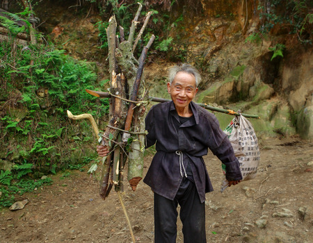 Zengchong village, Guizhou, China - April 11, 2010: An elderly Chinese man goes on a mountain road with a load on a yoke, carries a nylon bag and an armful of branches for the hearth, Zengchong village, Guizhou, China - April 11, 2010.