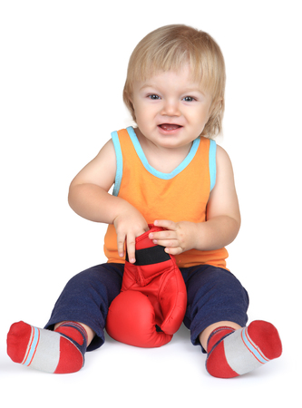 1 person: Small boy, 1 year old, light hair, Caucasian, in an orange tank top, in a sitting position, holding a boxing glove red and smiling, one person, vertical layout, isolated image on white background.