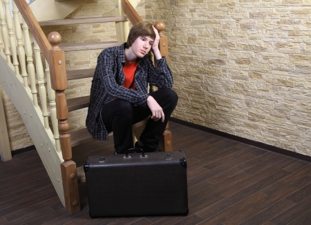 Pensive teenage boy 14 years old, in plaid shirt, sad sitting on the steps of a wooden spiral staircase next to a brown suitcase. photo