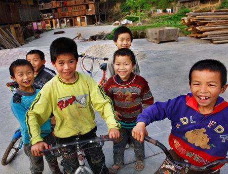 enfants qui rient: Zhaoxing Dong Village, province de Guizhou, Chine - 8 Avril 2010: Les Asie de l'Est, les enfants des zones rurales chinoises, rire, sourire et faire du v�lo dans le Zhaoxing Dong Village, province de Guizhou, Chine - 8 Avril 2010.
