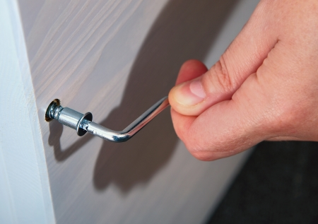 allen key: Assembling of furniture with a hexagon furniture key in hand of the master. Hand holds allen key furniture inserted into the bolt head.