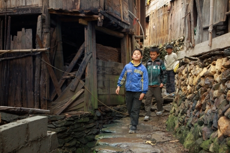 shortstop: Xiaozhai village, Guangsi province,China - April 5, 2010: Rural schoolboys teenagers, 12 years old, walking down the streets of the Chinese village in the mountainous countryside, April 5, 2010. Editorial