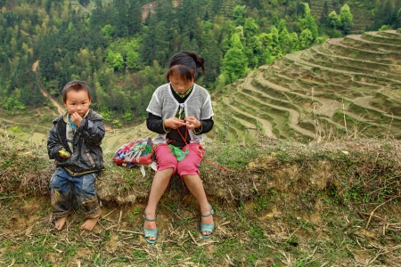 10 to 12 years old: Guizhou, China - April 10, 2010  Rural children in the highlands of China, sitting on the ground, amid rice terraces, farm land, the boy 4 years old, teen girl 12 years old, April 10, 2010  Basha Village, Congjiang County  Editorial