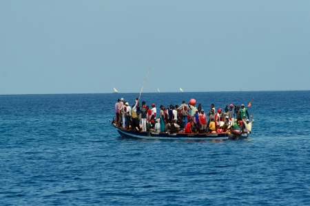 Zanzibar, Tanzania - February 16, 2008: Residents of Tanzania moved by boat between the islands, near Zanzibar, a large group of Africans standing in a heavily overburdened boat in the Indian Ocean, February 16, 2008.