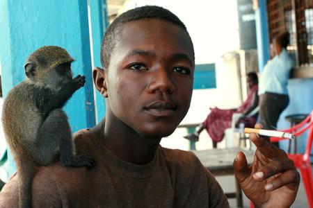 tame: Zanzibar, Tanzania - el 16 de febrero de 2008: Hombre africano joven de 25 a�os, fumando en un caf� al aire libre, con un cigarrillo, beb� manso mono verde que se sienta en su hombro, 16 de febrero de 2008. Un hombre negro con un mono entrenado en su hombro.