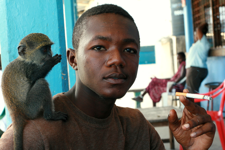 25 years old: Zanzibar, Tanzania - February 16, 2008: Young African man 25 years old, smoking at an outdoor cafe, holding a cigarette, tame baby green monkey sitting on his shoulder, February 16, 2008. A black man with a trained monkey on his shoulder.