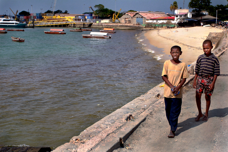 Zanzibar, Tanzania - February 16, 2008: Two dark-skinned African teenage boy, 12 years old, walking along the shore of the Indian Ocean, on a sunny day,  February 16, 2008.