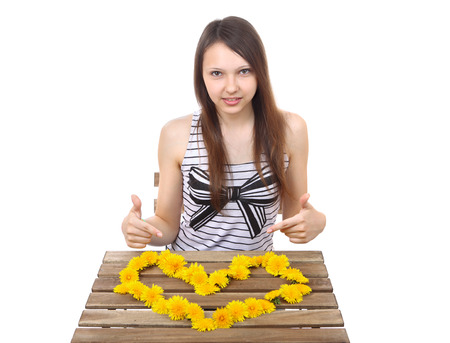 Caucasian teen girl, brunette, 15 years old, shows a yellow valentine made from dandelion flowers on the table surface  One person, image isolated on a white background  photo