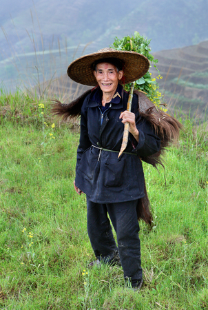 chinese hat: Yao Village Dazhai, Longsheng, Guangxi Province, China - April 3, 2010: One unidentified man in Asian Chinese hat and cape buffalo skins, stands on a background of rice fields and rice terraces in the agricultural regions of China. Editorial