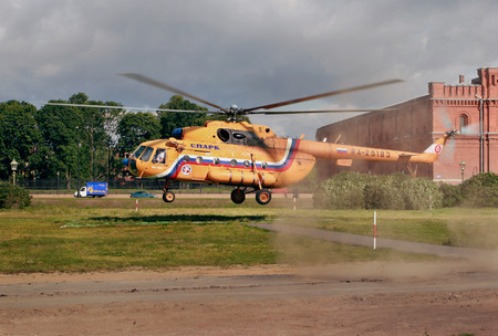 Russia, Saint Petersburg - July 19, 2007: Helicopter orange, Russian-made Mi-8, makes a landing on the grass lawn, near the Peter and Paul Fortress. Editorial use