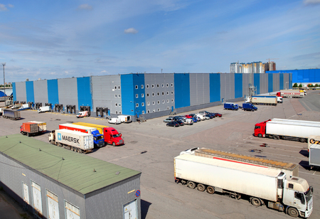 warehouse building: St. Petersburg, Russia - june 13, 2013:  Logistics facility, storage building, loading docks, parking for trucks, trailers in the parking lot in front of the warehouse storage Editorial