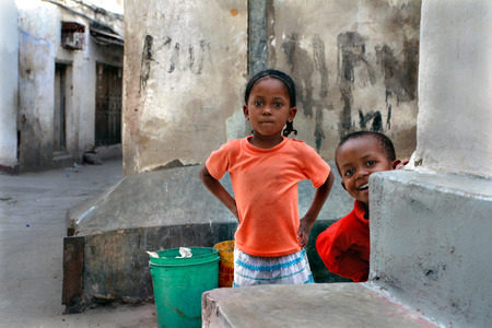 Zanzibar, Tanzania - February 20, 2008: The island of Zanzibar, Stone Town, unknown African, dark-skinned children, a boy and a girl, the approximate age of 5 years old, playing in the open air, in a narrow street of the city.