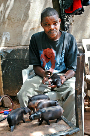 Namanga, Tanzania - February 9, 2008: Young black African man, a wood carver, working art workshop.  Dark-skinned master woodcarving, polishing wooden figurines of hippos.