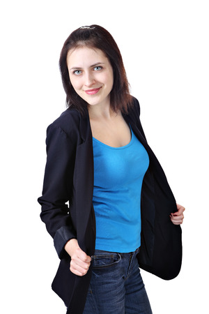Vertical portrait of one young smiling caucasian woman, 18 years old, dressed in a dark blue office jacket, light blue tank top and jeans trousers, isolated on white background. Stock Photo