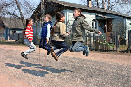 recess: Tver, Russia - May 2, 2006: Russian, rural junior schoolchildren during recess, jumping rope, on the road near the school