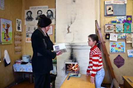 Tver, Russia - May 2, 2006: School teacher gives a lesson schoolgirl pupil in a school class room, next to a stone oven for wood heating, with burning firewood.