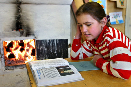 Tver, Russia - May 2, 2006: Russian schoolgirl reads textbook sitting beside an open fire wood stove.