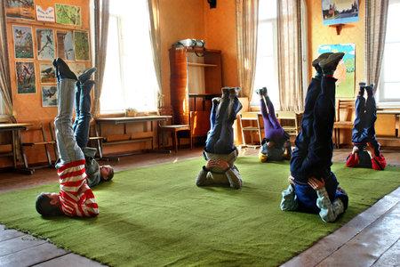 educacion fisica: Tver, Rusia - 2 de mayo 2006: los ni�os de la escuela las clases de educaci�n f�sica rurales que hacen ejercicio de hombro stand plantean, vela pose Editorial