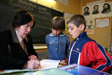 Tver, Russia - May 2, 2006: Rural school in the Russian countryside, children schoolchildren are watching as a schoolteacher checks homework. Stock Photo - 27268362