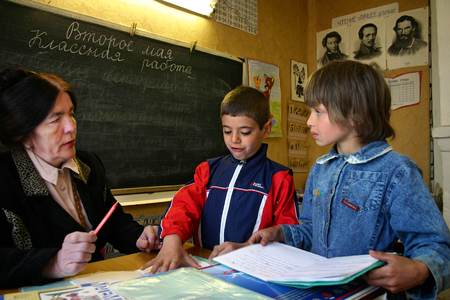 Tver, Russia - May 2, 2006: Rural school in the Russian countryside, children pupils, a boy and a girl standing near the teacher's desk. Stock Photo - 27268363