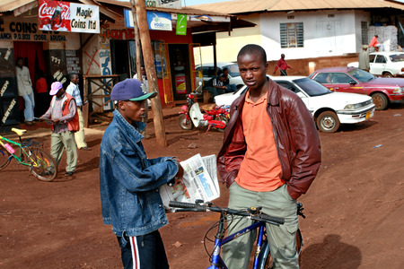 township: Makuyuni, Arusha, Tanzania - February 13, 2008: Young black African men met on the village street, one holding a newspaper Mwananchi, with text in Swahili, the other sits on the old bike.
