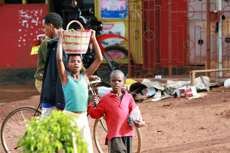 approximate: Makuyuni, Arusha, Tanzania - February 13, 2008: Unidentified African children, the approximate age of 10 years old, walking down the street of a small town., girl Carrying Baskets on Head, people carry heavy objects on their heads