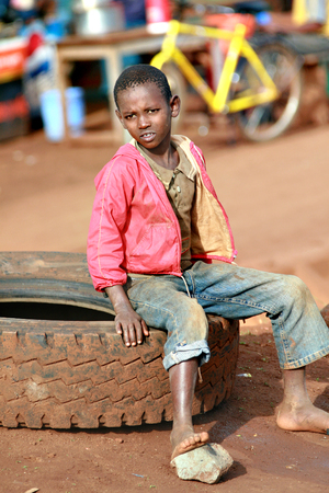 10 years old: Makuyuni, Arusha, Tanzania - February 13, 2008: Unknown African barefoot black boy in pink jacket, about 10 years old, has a rest sitting on a car tire Editorial