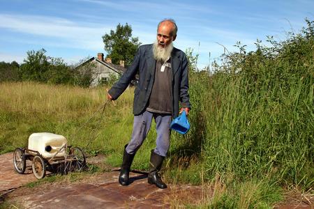 trundle: Leningrad area of St. Petersburg, Russia - July 22, 2006: Valentin Stepanovich Shramko born in 1938, Elderly, graybeard man peasant farmer pulls a cart with the canister well water.