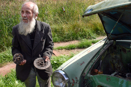 the outdated: Leningrad area of St. Petersburg, Russia - August 23, 2006: Valentin Stepanovich Shramko born in 1938, gray-bearded elderly peasant farmer, outdated car repairs, Old man holding a car clutch discs, engine cover opened
