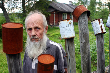Leningrad area of St. Petersburg, Russia - July 21, 2006: Valentin Stepanovich Shramko born in 1938, Portrait of a bearded old man on a background of red, wooden farmhouse. A villager stands behind picket fence on which dried empty tins.