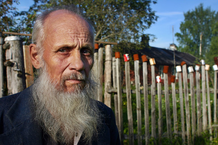agriculturalist: Leningrad area of St. Petersburg, Russia - July 22, 2006: Valentin Stepanovich Shramko born in 1938, Close-up portraits Russian peasant farmer, old age, gray-bearded, balding, photographed against a red wooden farmhouse, and the fence on which dried empty